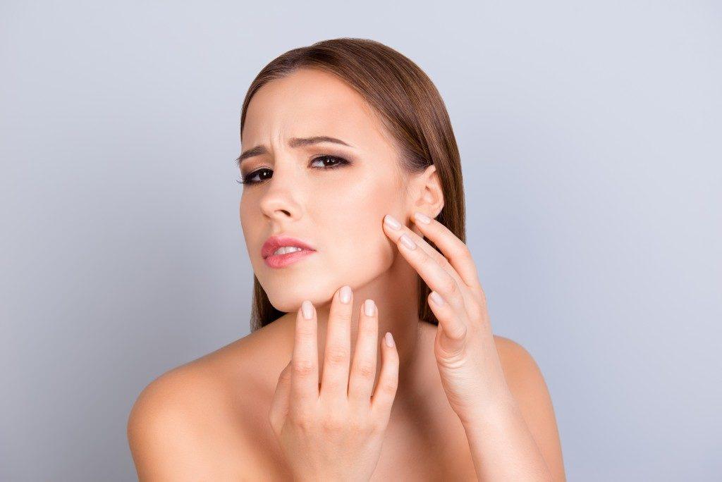 woman feeling her skin