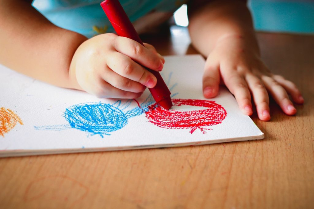 Child drawing using crayons