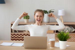 Happy millennial raising her hands