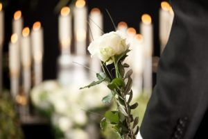 Man holding a white flower in the funeral