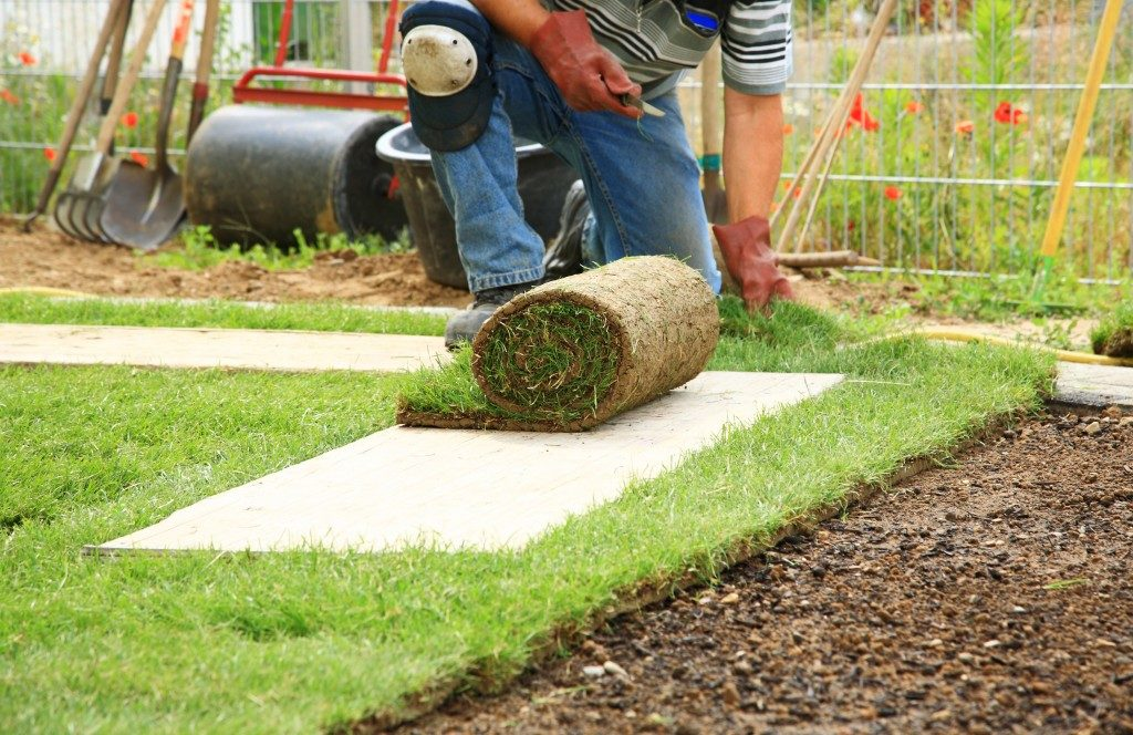 landscape worker laying fake grass