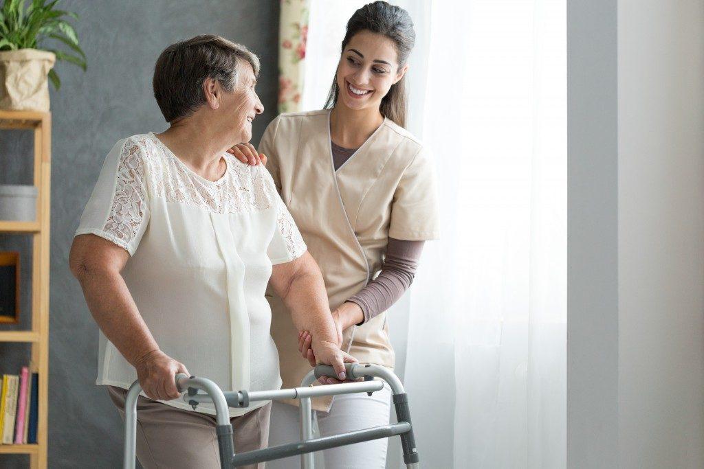 Caretaker guiding older woman