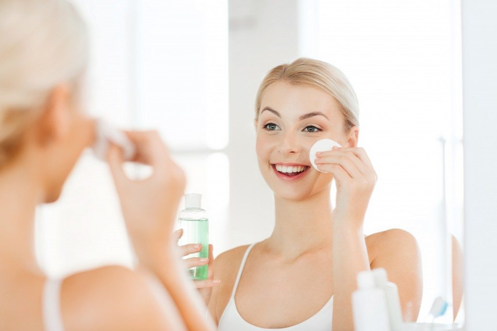 woman applying toner on her face