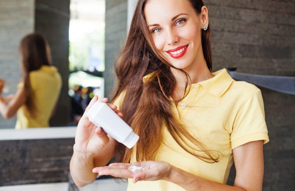Woman applying dry shampoo on her hair