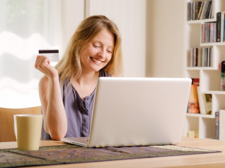 woman excited about online shopping with her laptop and credit card