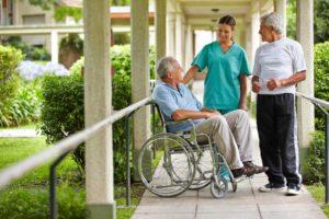 Two senior citizens talking to a nurse in a hospital garden