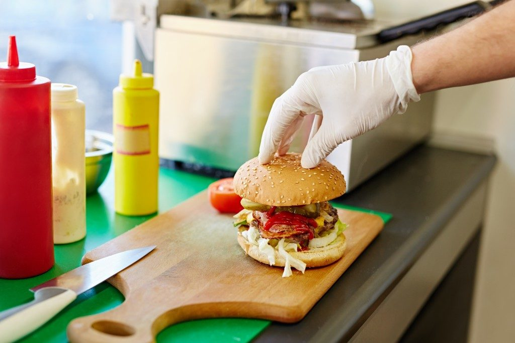 Cropped shot of a white latex gloved hand carefully putting the top bun down on a big delicious burger that's been freshly prepared