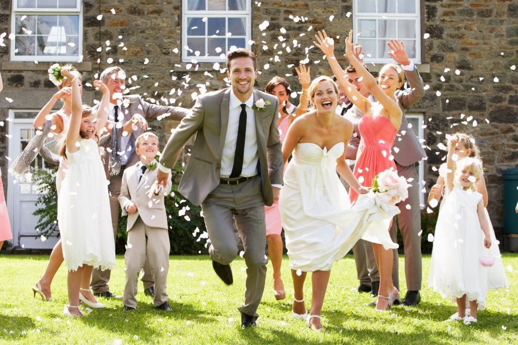people throwing confetti over bride and groom