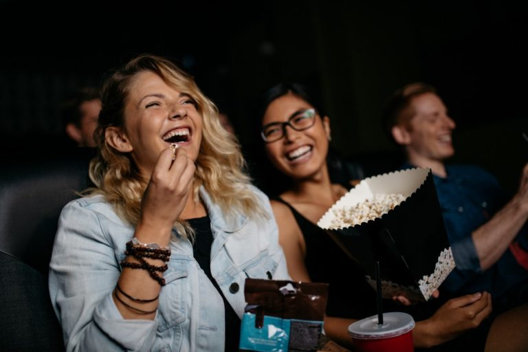 Friends watching a movie while eating popcorn