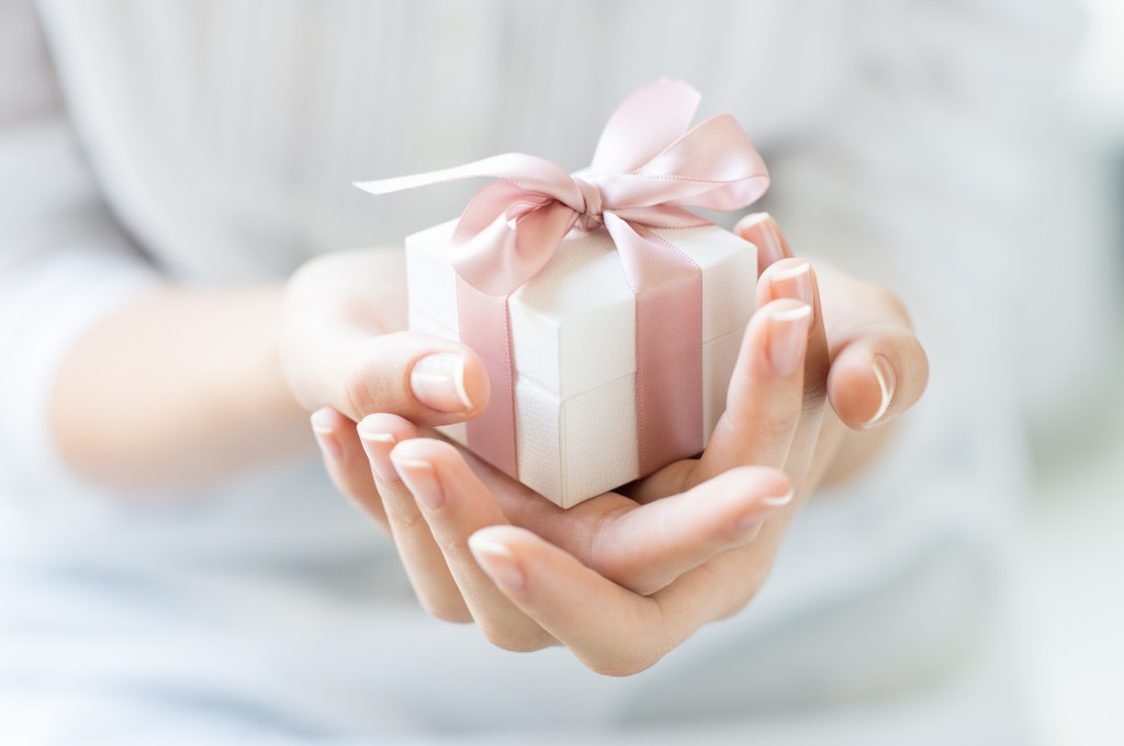 Close up shot of female hands holding a small gift wrapped with pink ribbon