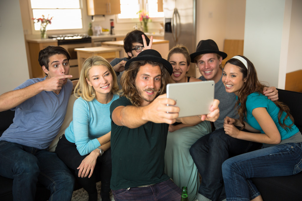 group of friends taking a selfie on a tablet are smiling