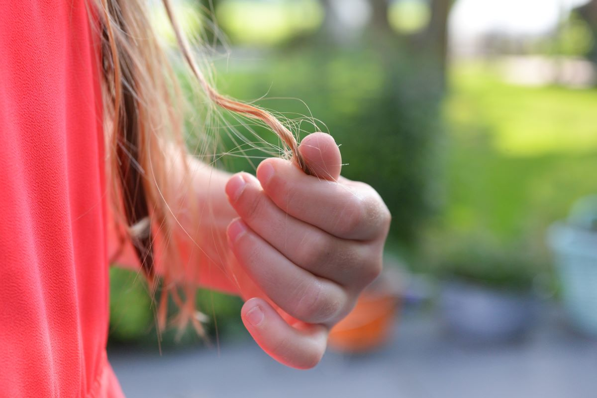 woman holding strands of hair