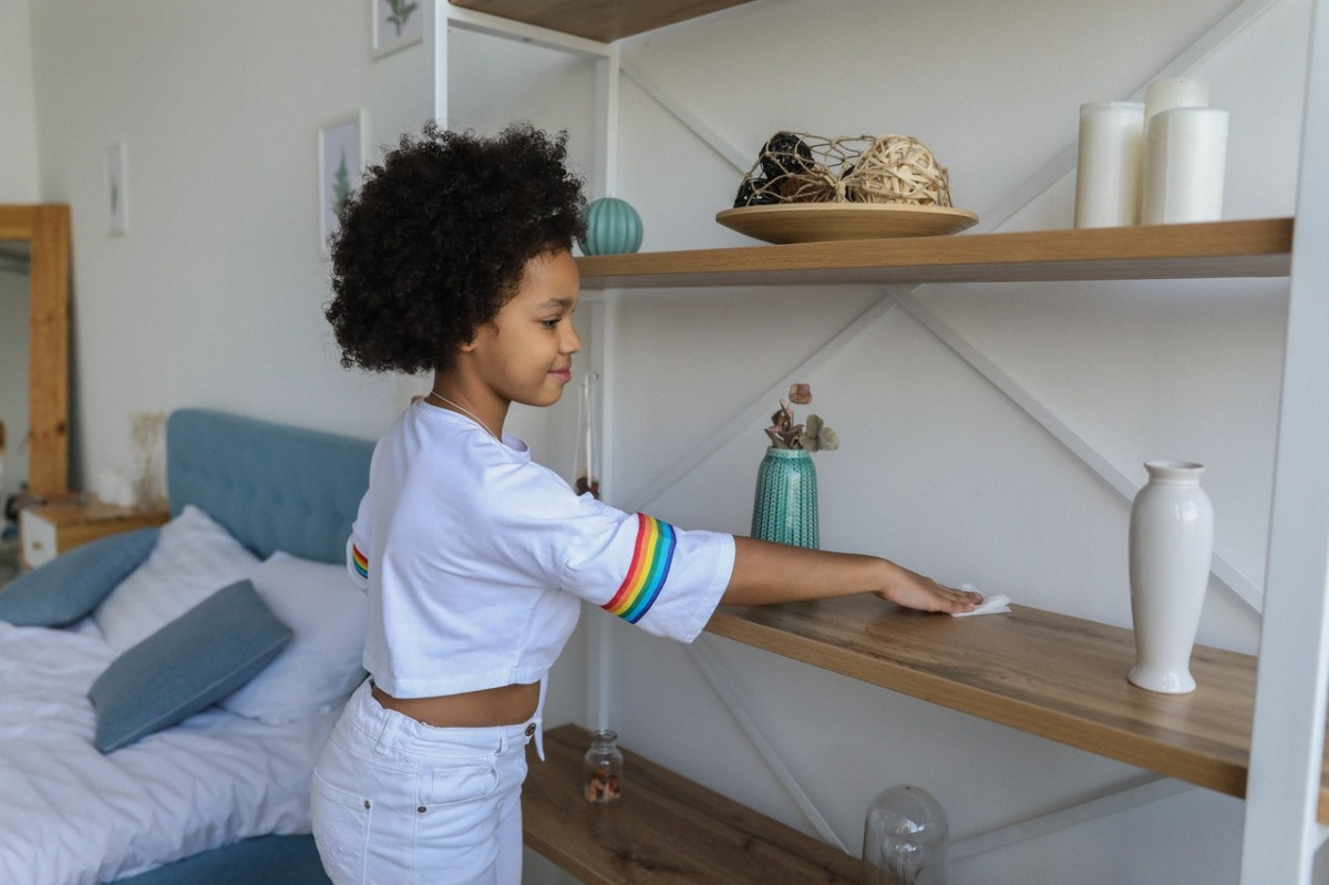 girl cleaning some shelves