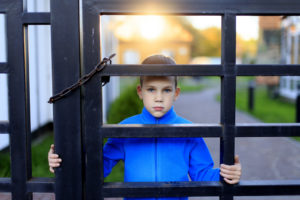 sad boy at the gate